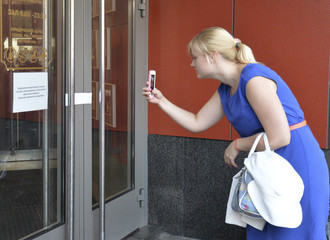 Woman takes a picture of a closed McDonald's restaurant in Moscow