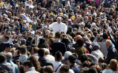 Pope Francis waves as he arrives at the weekly audience in Saint Peter's Square at the Vatican