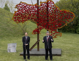 Ban Ki-moon and Poroshenko address the media in front of a symbolic map of Ukraine, constructed from red poppies, as they visit the Museum of Great Patriotic War in Kiev