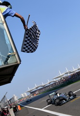 Mercedes Formula One driver Hamilton of Britain takes the chequered flag to win the Chinese F1 Grand Prix at the Shanghai International Circuit