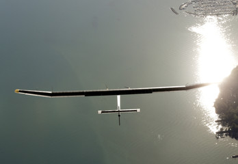 Solar Impulse's pilot Borschberg flies over the Neuchatel lake in the solar-powered HB-SIA prototype airplane after its first successful night flight attempt  in Payern