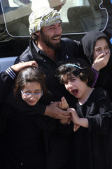 Mourners grieve for their relatives who were killed in Thursday's bomb attack, during a funeral in Najaf