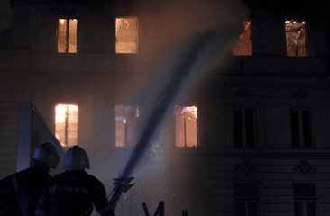 Firefighters work to extinguish the flames of a burning government building in Sarajevo