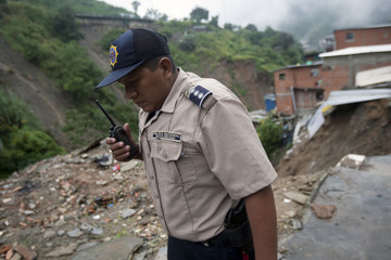 A police officer inspects a collapsed area during a landslide in the low-income neighborhood of Carretera Vieja in Caracas