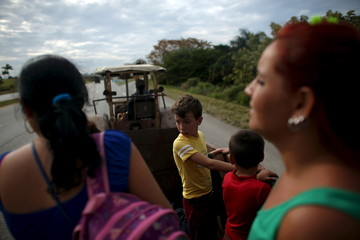 Sara Carcache drives her Ukrainian made tractor as she takes children and their mothers from school in Caimito
