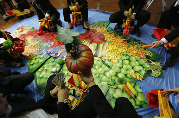Activists hold out plastic vegetables as they ride toy excavators and bulldozers on a large map featuring pictures of food in the shape of the African continent during a protest in Tokyo