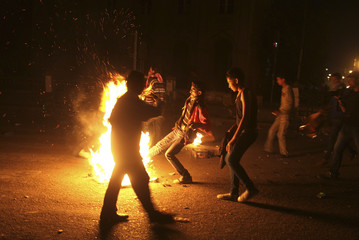 A protesters throws more objects into a fire during clashes with police in front of the High Court in Cairo