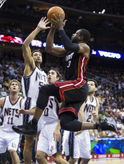 Miami Heat Dwyane Wade drives past New Jersey Nets Lopez, Gadzuric, Vujacic and Farmar to score in their NBA basketball game in Newark