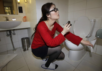 Zhuang Jing checks the texture of the toilet paper at a business chain hotel, in Beijing