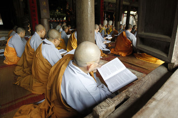Buddhist nuns recite Buddhist scriptures during a summer class in Thay pagoda, outside Hanoi