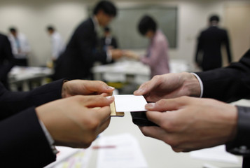 Japanese job-hunting students dressed in suits practice swapping business cards during a business manners seminar at a placement centre in Tokyo