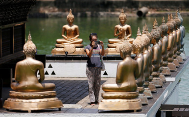 A tourist takes pictures of Buddha statues at a temple in Colombo