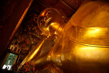 A tourist takes a picture of the sculpture of the reclining Buddha at Wat Pho temple in Bangkok