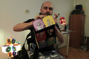 Romanian actor Alin Teglas works on a purse made from used floppy disks in his kitchen-workshop in Bucharest