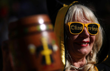 """A woman holds her beer mug as she wears sunglasses that reads """"Oktoberfest"""" at Argentina's Oktoberfest, the national beer festival, in Villa General Belgrano, Argentina"""