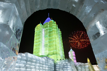 An ice sculpture is seen as fireworks are lit in the background during the 26th Harbin International Ice and Snow Festival at a park in Harbin