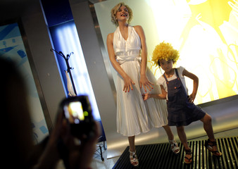 A girl posses for a picture with a wax statue of actress Marilyn Monroe at the Madame Tussauds Wax Museum in Shanghai