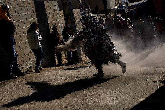 "A man wearing a ""La Filadorra"" (The Spinner) mask throws ashes during the ""Los Carochos"" winter masquerade in Riofrio de Aliste, Spain"