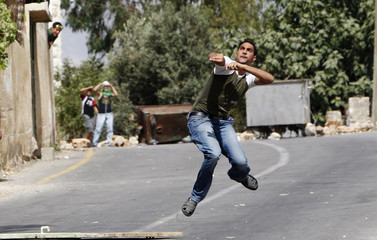 A Palestinian throw stones at Israeli security forces during clashes in the West Bank village of Nabi Saleh near Ramallah