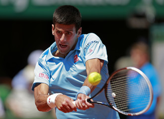 Novak Djokovic of Serbia returns the ball to Ernests Gulbis of Latvia during their men's semi-final match at the French Open tennis tournament at the Roland Garros stadium in Paris