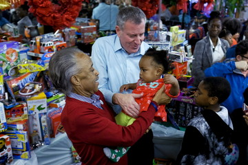 New York City Mayor de Blasio, and civil rights activist Sharpton holds up a baby as they give presents to children during an event celebrating Christmas at the National Action Network in Harlem, New York