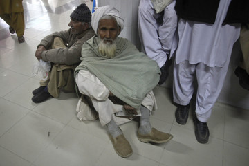Men sit on the floor amid others waiting to receive free medication from a pharmacy at the Punjab Institute of Cardiology (PIC) in Lahore