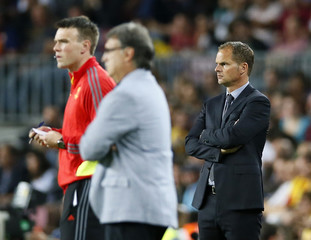 Fourth official Midthjell of Norway,  Barcelona's coach Martino and Ajax's coach De Boer watch from the touchline during their Champions League soccer match at Camp Nou stadium in Barcelona