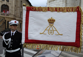 A Monaco's policeman stands next to a flag with the monogram of Albert II of Monaco in front of the cathedral for the Monaco's National Day in Monte Carlo