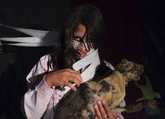 """A Bolivian actress performs in a """"haunted house"""" as part of Halloween celebrations in El Alto"""