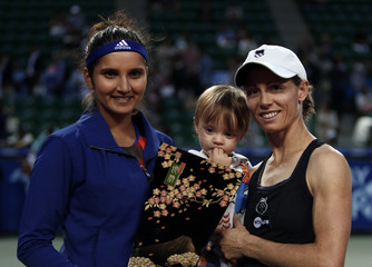 Black of Zimbabwe holding her son Lachlan and Mirza of India holding their victory trophy pose for photographs after defeating Taiwan's Chan and Huber of U.S. during their women's doubles final match at Pan Pacific Open tennis tournament in Tokyo