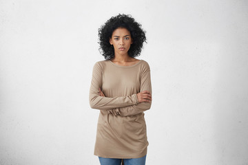 Indoor studio shot of angry young dark-skinned housewife in casual clothes standing in closed posture, keeping arms folded, mad at her drunk husband. Unhappy woman feeling insulted or offended