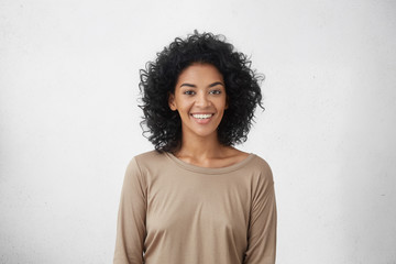 Waist up portrait of cheerful young mixed race female with curly hair posing in studio with happy smile. Dark-skinned woman dressed casually smiling joyfully, showing her white straight teeth Wall mural