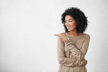 Attractive smiling young female customer with curly hair looking sideways and pointing her index finger at copy space on white blank studio wall for your text or promotional content. Horizontal