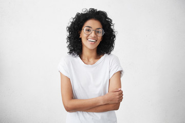Charming young dark-skinned woman with curly hairstyle having shy smile posing in studio in closed posture, keeping arms folded, feeling constrained and a bit nervous. Human emotions and feelings