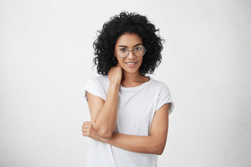Human emotions, feelings, reaction and attitude. Charming cute girl with louse shaggy hair dressed in casual t-shirt posing indoors in closed posture, rubbing neck, feeling nervous and uncomfortable