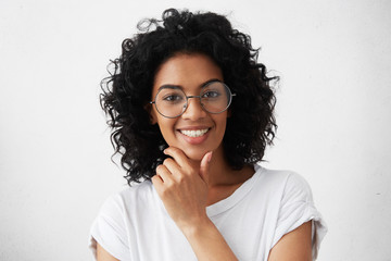 People and lifestyle. Youth and happiness. Close up portrait of confident dark-skinned girl with curly hairstyle posing against white studio wall with copy space for your advertising information