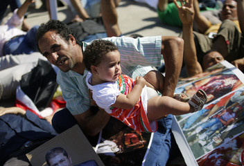 A man holds a baby during a demonstration in support of ousted Egyptian president Mohamed Mursi in Rome