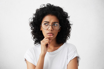 Isolated portrait of stylish young mixed race woman with dark shaggy hair touching her chin and looking sideways with doubtful and sceptical expression, suspecting her boyfriend of lying to her