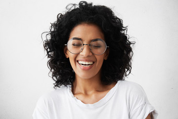 Pretty girl with dark clean skin and beautiful toothy smile laughing out loud at funny joke while having fun indoors with friends, closing eyes in joy, looking carefree and relaxed. Horizontal