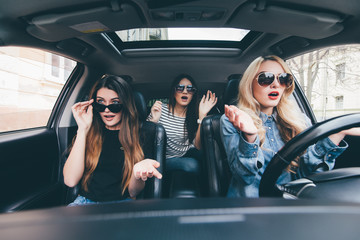 Three girls are sitting shocked and scare before damage during the car driving