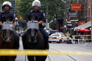 Police officers investigate scene of fatal shooting that left one dead and another injured at Sicilian Sidewalk Cafe in Toronto