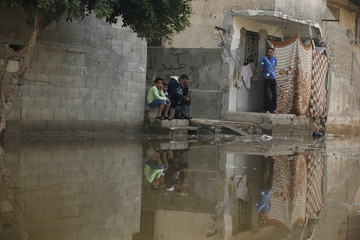 Palestinians sit outside their houses on a street flooded with sewage water from a sewage treatment facility in Gaza City
