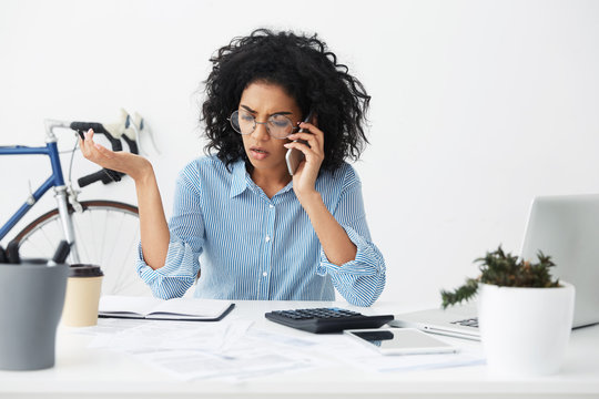 Businesspeople, modern technology and communication. Upset mixed race businesswoman having stressful phone conversation, calling customer service about budget or invoice problem, gesturing actively