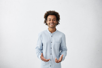 Handsome young African American male wearing light long shirt smiling and gesturing with both hands, having clueless expression on his face, standing at white wall with copy space for your text