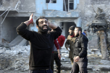 A man with blood stained hand reacts at a damaged site after what activists said was heavy shelling by forces loyal to Syrian President Bashar Al-Assad, in Masaken Hanano neighbourhood in Aleppo