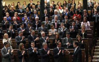 Spain's People's Party leader and incoming PM Rajoy is applauded by his fellow party deputies after delivering his speech during the investiture debate at Parliament in Madrid