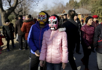 Two girls wearing Beijing Opera masks pose for a photo at a Spring Festival temple fair on the second day of the Chinese Lunar New Year of the Monkey in Beijing