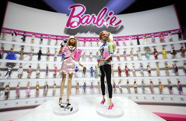 Mattel's newly-introduced News Barbie and Computer Engineer Barbie are shown in front of a display of career-doll Barbies at the Toy Fair in New York