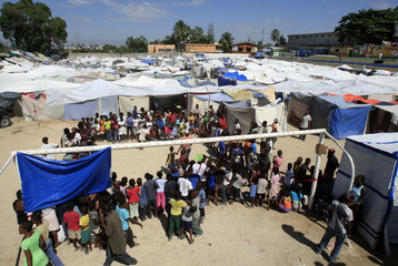 People wait in line during food distribution at a makeshift camp on a soccer field in Port-au-Prince, Haiti