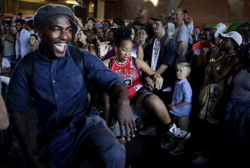 Boy watches people dance in the style of the Soul Train line from the 1970s TV series at a celebration of street culture on the South Bank of the river Thames in London